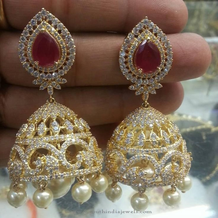 Beautiful one gram gold wedding jhumki designs embellished with rubies and pearls. For inquiries please contact the seller below. Seller Name : Brundavan Jewellery Contact No : 07702837417 More CollectionsGold Plated Antique Temple JhumkaMatt Finish One Gram Gold JhumkasOne Gram Gold Bridal Jhumka From SwarnakshiOne Gram Gold Hoop Jhumka EarringsOne Gram Gold Stone Jhumki1 Gram
