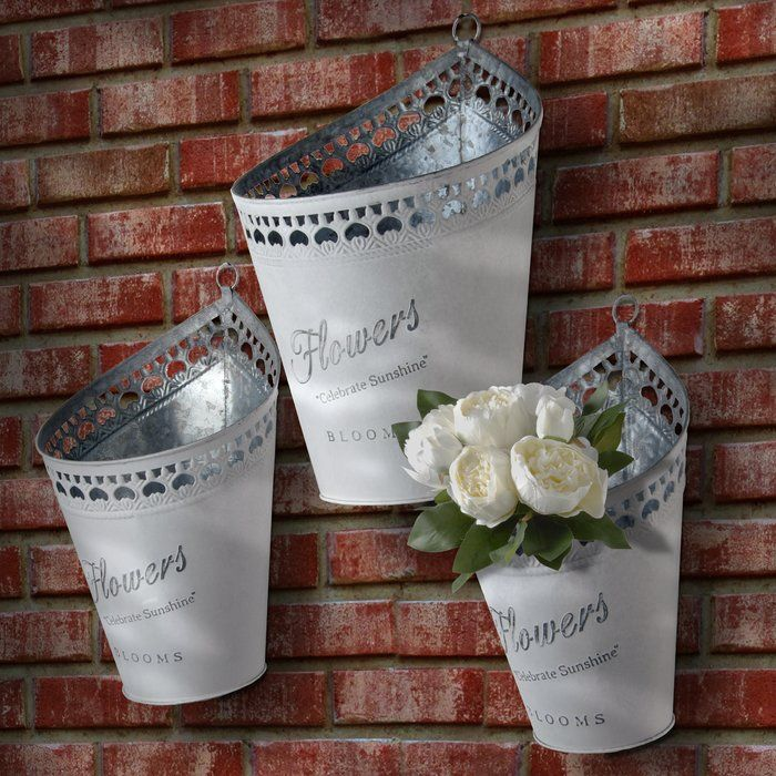 This set of galvanized steel pots are perfect for containing small plants or flowers. Each pot features an ornate cut out design along the rim with round front to unique up-pointed back. The painted exterior contains printed wording: Flowers; celebrate sunshine; blooms. These practical yet rustic decorations can be displayed on tabletop or hung using the attached loops. For indoor or outdoor use.