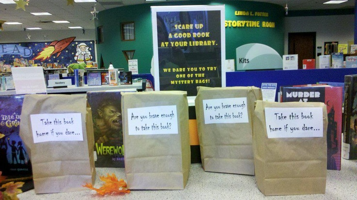 """Created Halloween display with horror & mystery genres; put some in brown paper bags with labels like """"Take this book home if you dare..."""" and """"Are you brave enough to take this book?""""  The promo sign reads: """"Scare up a good book at your library.  We dare you to try one of the mystery bags.""""  So popular, the younger readers want their own mystery bags! at SMFPL"""