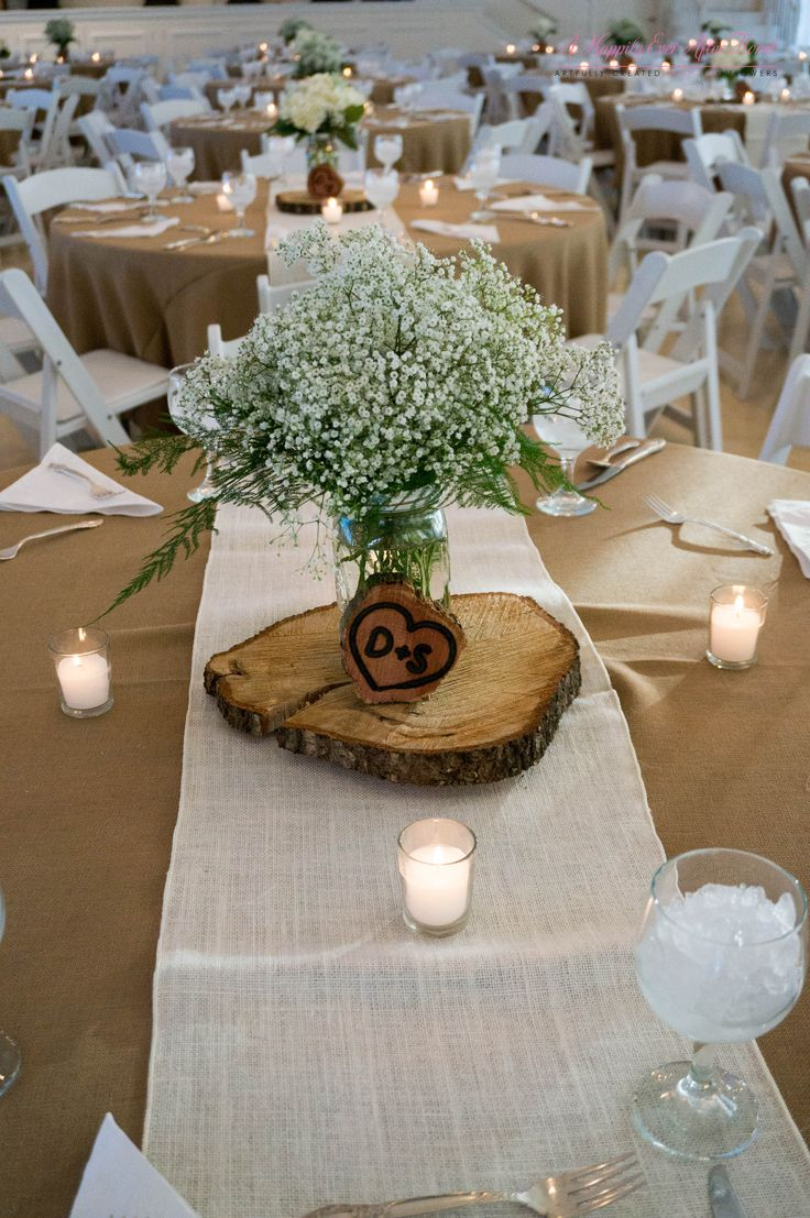 babies breath centerpiece sitting on top of wooden disk