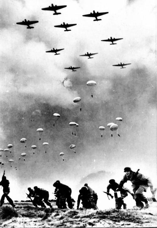2 World War, planes dumping soldiers in parasuits, some has already landed, and are running to seek cover. Photo b/w, history.