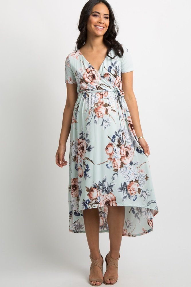ceb5d4b438967 A floral print, hi-low maternity midi dress featuring a wrap v-neckline,  elastic cinching under the bust, short sleeves, and belt loops with a sash  tie.