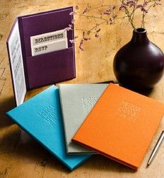 Custom and hand made wedding pocket invitation panels in four colours with blind embossed names on the covers.