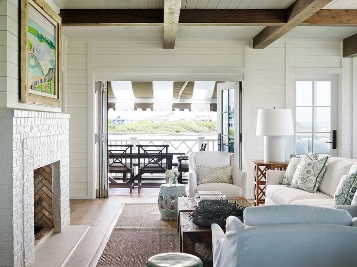 Beach cottage living room features a shiplap ceiling finished with dark wood beams placed over a shiplap fireplace wall lined with art over a white brick fireplace accented with a red brick fireplace.