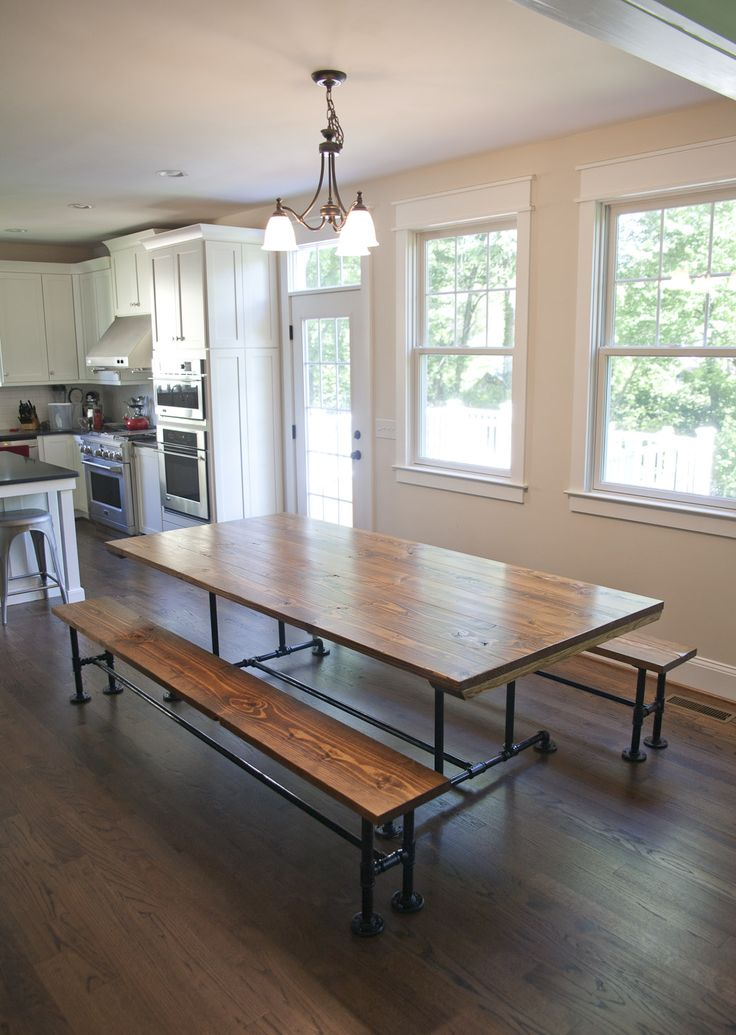Industrial farmhouse style table. The dark walnut top and black industrial piping looks good with the white molding. DC Metro Area kitchen. Craftsman style home.