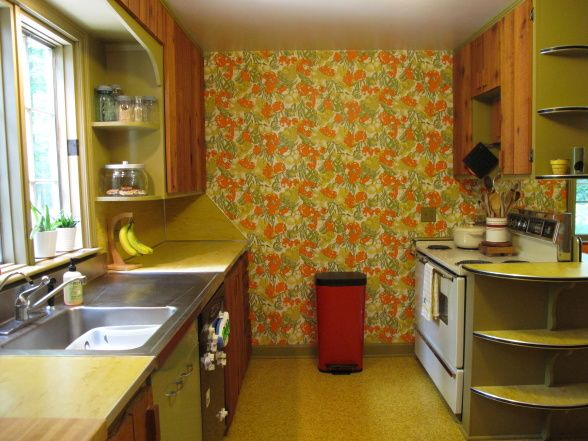 kitchen is straight out of the 60s with bold veggie wallpaper, linoleum counter tops, rough cedar cabinets (with orange interior), and bright orange seating nook. //love this all original vintage retro 60s 70s kitchen :)