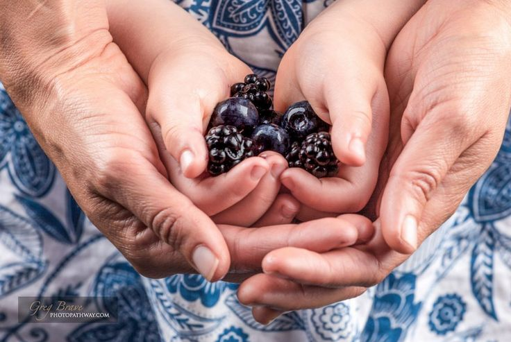 Female hands embracing child hands holding blackberries and blueberries closeup