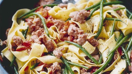 Skär ner salsicciakorven och stek några minuter i olivolja. Tillsätt vitlök och stek ytterligare någon minut. Häll i tomater och vitt vin och låt koka ihop ca 3 minuter. Koka pastan enligt anvisning på paketet. Koka med haricots verts sista minuterna. Blanda sedan med såsen och smaka av med salt och peppar.