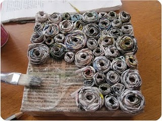 Newspaper coils on (recycled) canvas. Bet it would look smashing with FABRIC coils, too.