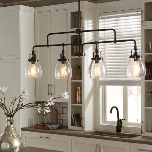 Influenced by the vintage industrial designs of early 20th Century America, the transitional Belton lighting collection by Sea Gull Lighting has Seeded glass shades that highlight the classic Edison bulbs. The rich Heirloom Bronze finish adds another layer of retro design to the warm look. The assortment includes three- and five-light chandeliers; a four-light island pendant; one-light pendant; one-light mini pendant; and one-, two-, three- and four-light bath fixtures.  Material: Clear…
