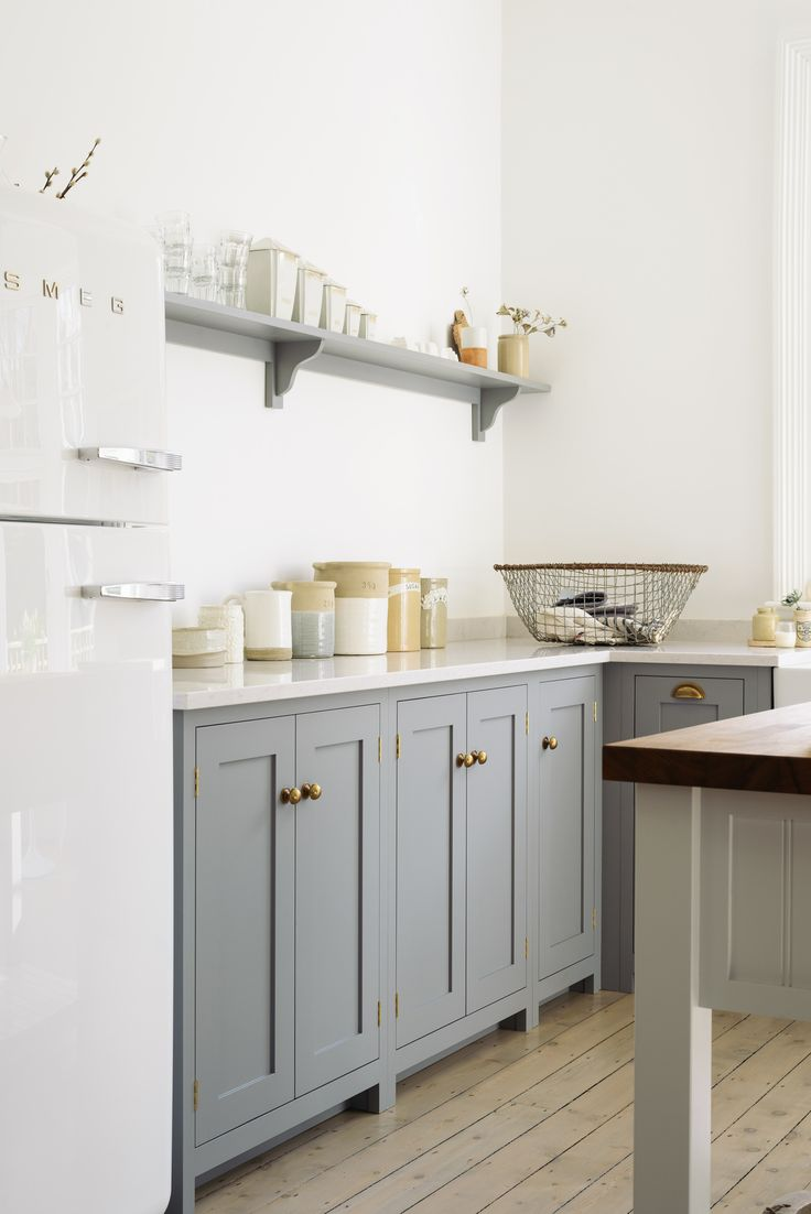 Beautifully simple deVOL Shaker cupboards with brass door furniture and sleek 'Lagoon' Silestone worktops, a white Smeg fridge, a few vintage pots and some lovely linens... the dream family kitchen