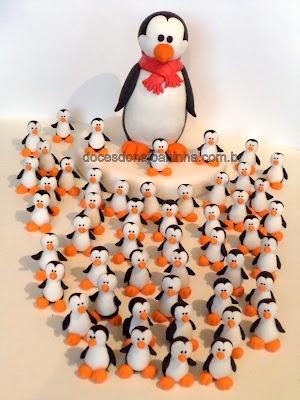 Pinguim rodeado de docinhos no formato de pinguim para decorar bolo e mesa de docinhos.
