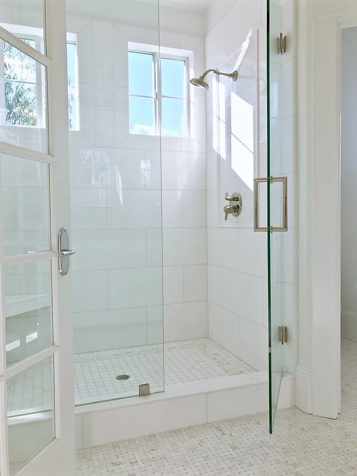 "Beautiful light, airy white shower with white 12"" x 24"" Akdo Thassos tiles and white and light gray basketweave floor tiles, glass is coated with Diamond Fusion to help protect it from water stains."