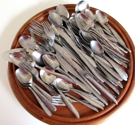 Large Mixed lot of Modern Era stainless steel Flatware! All have some sort of starburst on the handle. Some have a swirl or a line or a shaping detail at the handle tip. 85 piece Lot includes 11 salad forks 11 dinner forks 26 dinner knives 9 soup spoons 20 tea spoons 3 parfait or iced tea spoons 5 serving pieces (pie server, pierced spoon, serving spoon, ladle, sugar spoon)  Brands include Oneida Community, Mar-crest, Wallace (more)  Patterns include Americana Star, Starette, Etoile(more)…