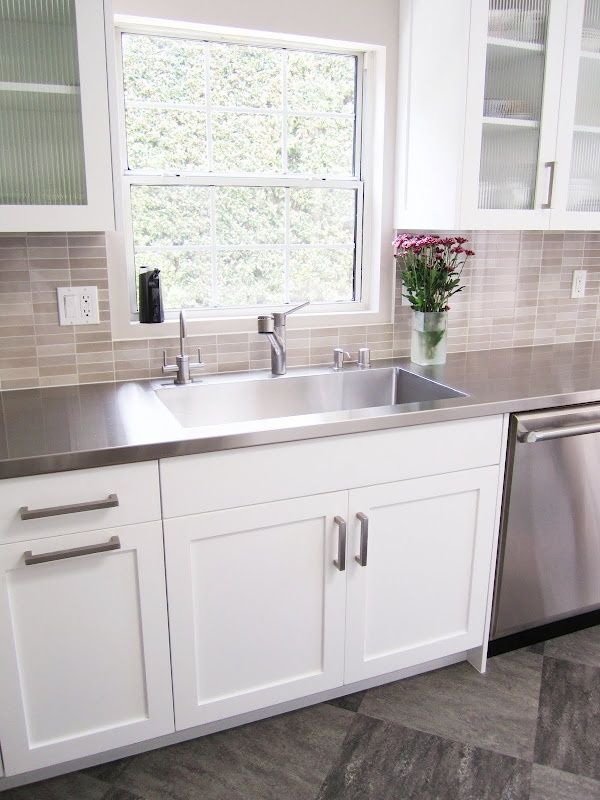 Stainless steel counters with integrated stainless steel sink. White cabinets. Glass tile backsplash. Photo by Coco of COCOCOZY