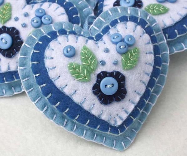 Felt hanging heart with layers of applique and embroidery in blues and white, embellished with tiny buttons. A perfect gift or decoration . 9cm x 8cm approx, with a ribbon loop for hanging. Please cho