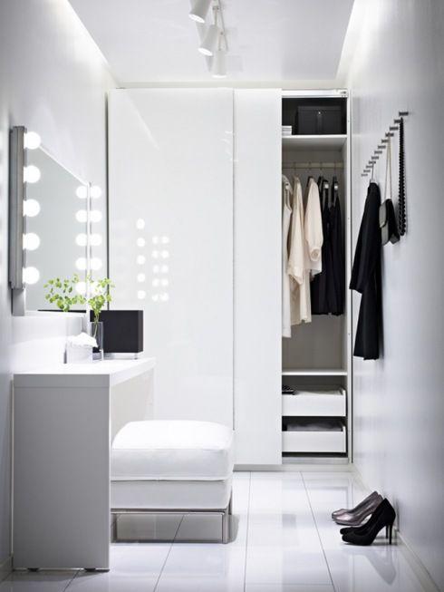 bialy przedpokój z biała podłogą,biała szafa z przesuwnymi drzwiami,biały puf z konsolką