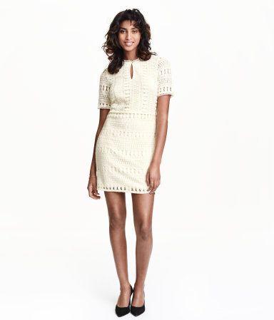 Kort kjole i gennembrudt blonde. Den har korte ærmer og er skåret i taljen. Knaplukning foroven. Foret for- og bagstykke.