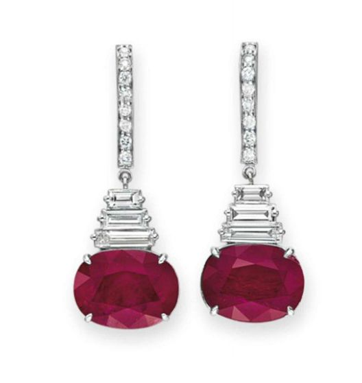 A PAIR OF RUBY AND DIAMOND EAR PENDANTS Each suspending a horizontally-set oval-cut ruby, joined by three baguette-cut diamonds to the circular-cut diamond line, mounted in 18k white gold