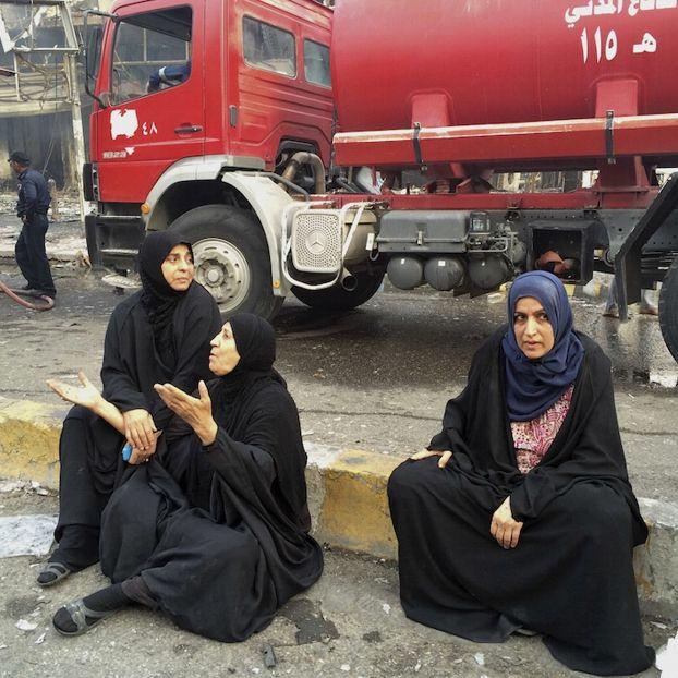 Tre donne irachene aspettano di sapere cosa sia successo ai loro famigliari dopo l'esplosione di un'autobomba nel quartiere di Karrada, a Baghdad