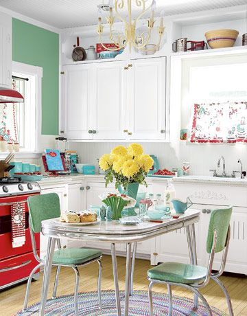 Delightful retro kitchen with green walls matching the vintage chairs and table top.  Red range adds a pop of color that is picked up with the window curtain made from vintage linens.  Display space across the top of cabinets and window is a ncie touch.