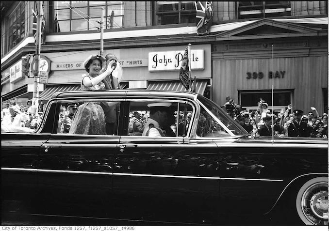Queen Elizabeth II in automobile, moving past spectators on Bay Street 1959