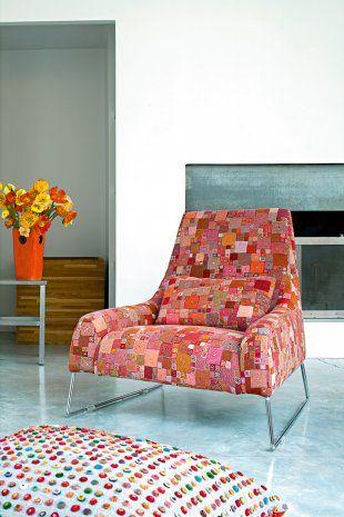 Dans le salon blanc et orange, place à la fantaisie avec du mobilier coloré.