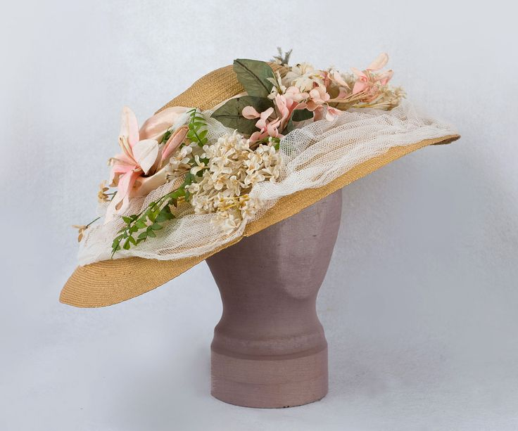 Wide-brim straw hat with floral decoration, c.1905. Made from natural colored straw, the hat boasts the elaborate floral decoration so popular during the Edwardian period. Shirred ivory cotton tulle and pink satin ribbon complete the tableau. vintagetextile.com