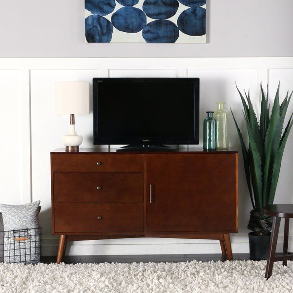 """Your living or entertainment room can look even more stylish with this 52"""" Mid-Century TV Stand. This piece of furniture offers ample storage for your media components, gaming devices, other electronic accessories. Crafted from durable manufactured wood, this flat panel TV stand is designed for TVs up to 55"""" wide. The versatile design features three large drawers, side cabinet with adjustable shelving and a cable management function at the back."""