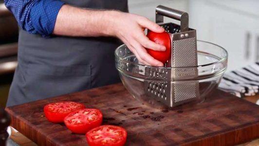 El frota un tomate crudo sobre un rallador de queso. Ahora préstale atención al bol …