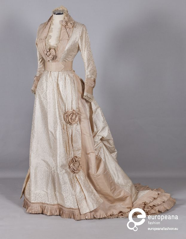 1870 Ivory brocade two piece bustle wedding dress with woven paisley motifs, trimmed with beige organza bows and pleated beige taffeta frills: tied fitting bodice and long skirt with train.