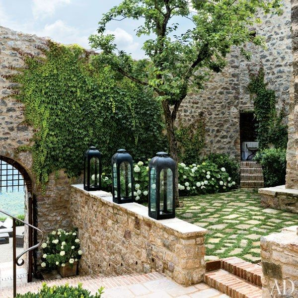 Custom-painted lanterns by RH mark an entrance that was rebuilt with a brick-and-stone staircase | archdigest.com