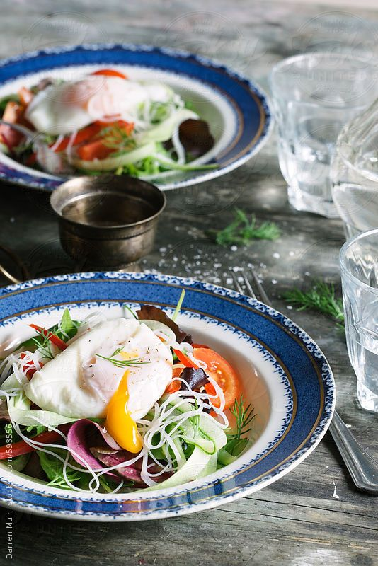 Two plates with vermicelli and poached egg salads. by DarrenMuir | Stocksy United