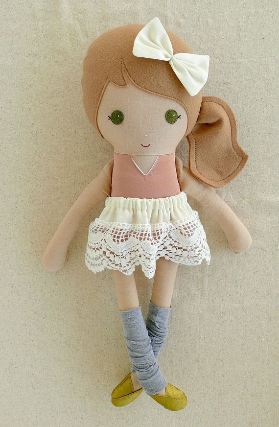 A handmade cloth doll measuring 20 inches. She is wearing a lovely salmon-pink, satin leotard with a removable cream lace skirt, gray leg warmers, and gold shoes. Her light brown hair is worn in a low, side ponytail and accented with a matching fabric bow. She is made from 100% cotton fabrics, cotton lace, wool blend felt, and polyester fiberfill. Her seams are triple stitched and she is firmly stuffed with Polyfil.   Please hand wash or machine wash on gentl...