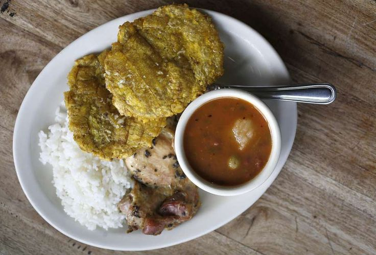 Pollo al Horno — baked chicken thighs, served here with rice, pink or black beans, and tostones con mojo. Photo: Liz Hafalia, The Chronicle
