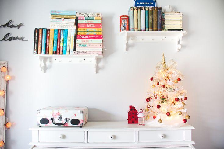 Quarto com decoração natalina e árvore de natal branca em cima da escrivaninha.
