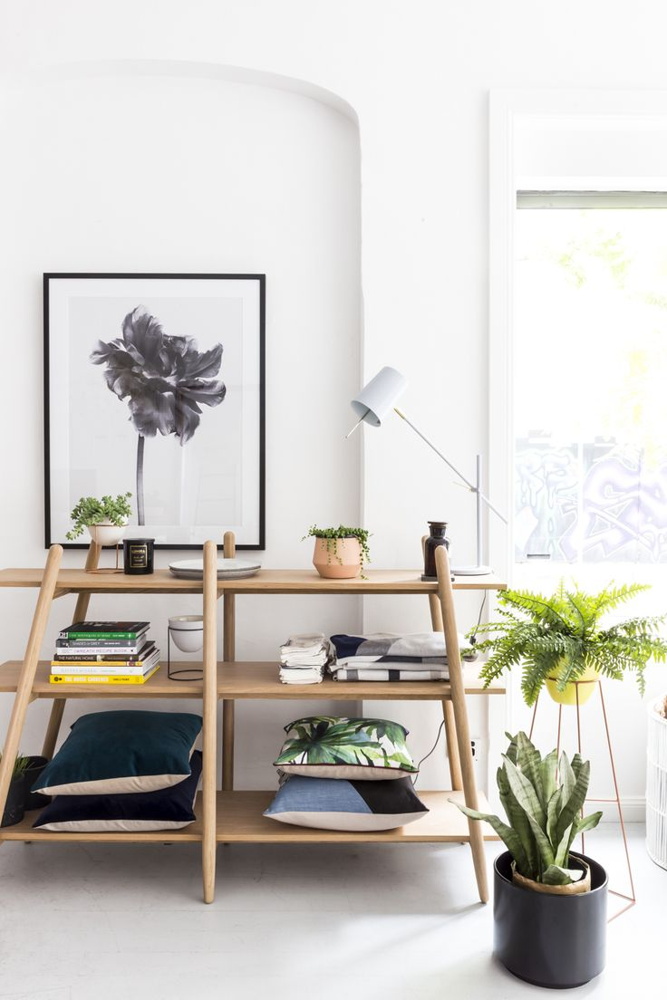 Oh yes. This shelving unit's warm timber and play with angles mean pretty much anything looks good displayed on it. These cushions and planter pot add some colour, while the monochrome framed art print on the wall keeps it classic.