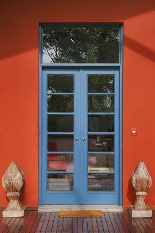 Uma porta que é um convite para receber amigos e acolher a felicidade. Cores vivas e vibrantes nessa casa de fazenda, projeto de Marina Linhares.