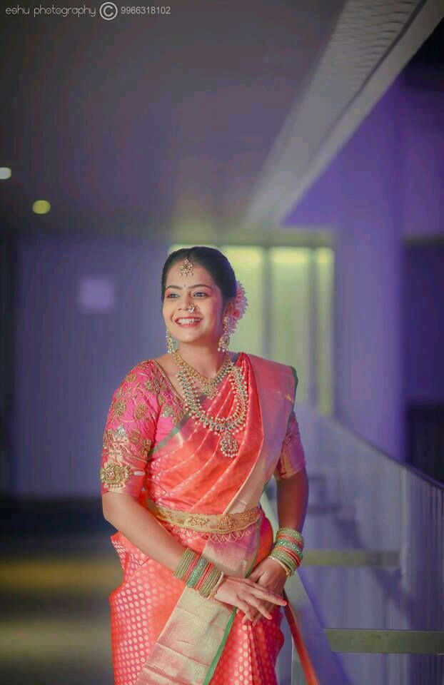 South Indian bride. Gold Indian bridal jewelry.Temple jewelry. Jhumkis.Coral pink silk kanchipuram sari.Side braid with fresh jasmine flowers. Tamil bride. Telugu bride. Kannada bride. Hindu bride. Malayalee bride.Kerala bride.South Indian wedding.
