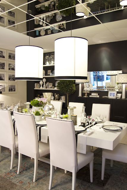Black and white dining theme..I am digging the throwback to the 60's w/the MIRRORED ceiling, with the sleek modern details in the room this works. This room wld be a bit boring in my opinion w/o the HUGE pendant lights w/BIG SHADES trimmed in black...like the black accent wall and gallery of pictures too..