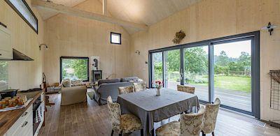 Interiér domu je rozdělen do dvou výškových úrovní, mezi nimiž je jeden schod. V té nižší je hlavní obytná místnost s kuchyňskou zónou.