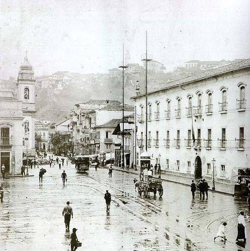 Rua Direita [hoje Primeiro de Março]. Convento do Carmo à esquerda. Pedaço do Paço à esquerda. Torre da Igreja de São José à esquerda. Morro do Castelo ao fundo. Av. Antonio Carlos não era nascida.