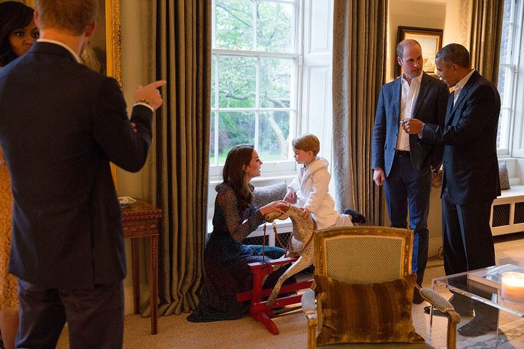 President Barack Obama talks with the Duke of Cambridge while the Duchess of Cambridge plays with Prince George on rocking horse