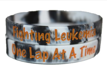 """Show your support for families fighting Leukemia with this Racing 2 Cure wristband. Featuring black and white checkered swirl and writing in Leukemia orange. This wristband comes in two sizes Adult and Youth.  The outside of the wristband reads """"Fighting Leukemia One Lap at a Time,"""" while the inside has the Racing 2 Cure website. 100% of the proceeds from the purchase of this wristband directly benefits families dealing with cancer. Each wristband was also made in the USA and comes in its…"""