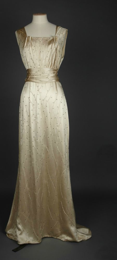 Dress [front view], England, 1934-35. Springhill Costume Collection © National Trust / Andrew Patterson. A presentation outfit consisting of a cream silk slipper satin long dress with a cowl neck line centre front, pleated into the centre back, with a decoration of random wavy tucks and scattered claw set, flat backed diamante all over. Cut to a slight train centre back, the dress is straight with a normal waist. An elegant dress. The detachable train gives it a second use as an evening…