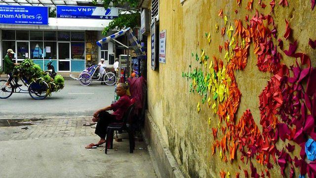 """Ein wundervolles Projekt der französischen Künstlerin Mademoiselle Maurice, die ein paar """"Urban Origami Installations"""" an Häuserfassaden in Vietnam, Hong Kong und Frankreich gebracht hat. Hunderte von gefaltenen Origami-Figuren aus leuchtenden Farben wurden in verschiedenen, geometrischen Formen an die Wände gebracht, in Vietnam z.B. der Stern der vietnamesischen Nationalflagge. Angefangen hat Mademoiselle Maurice mit diesem Projekt übrigens nach dem Fukushima-Unfall im... Weiterlesen"""