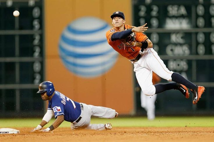 HOUSTON, TX - JULY 17: Carlos Correa #1 of the Houston Astros throws to first base over a sliding Delino DeShields #7 of the Texas Rangers in the fifth inning at Minute Maid Park on July 17, 2015 in Houston, Texas. (Photo by Bob Levey/Getty Images)