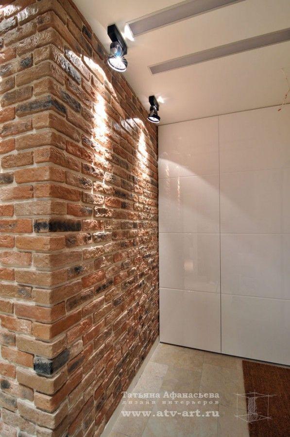 """Прихожая: светлый пол, белый плинтус, белая мебель, """"кирпичная"""" стена."""