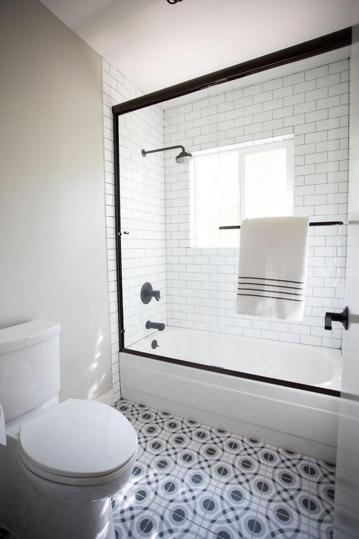 A black frame surrounding the glass shower door creates a bold color contrast and timeless combination with the white subway tile shower interior. A patterned black and white tile floor adds intrigue to simple style of the design. Black details pop for a crisp and attractive finish.
