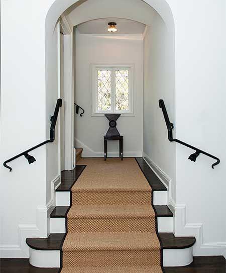 White walls, black trim, natural brown carpet runner. That little chair is pretty cool too.